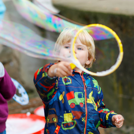 three years old: Three years old caucasian toddler boy blowing soap bubbles outdoor on birthday party - happy carefree childhood. Kid having fun. Stock Photo