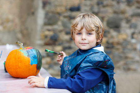 a small painting: Happy little kid boy on a harvest festival, painting with colors a pumpkin. Child celebrating traditional festival halloween or thanksgiving. Stock Photo
