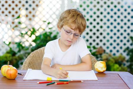 preescolar: Retrato de lindo niño feliz niño preescolar con gafas en la toma de la casa los deberes. Pequeño niño pintar con lápices de colores, en el interior. Escuela, concepto de la educación