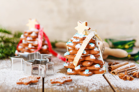 als: Homemade baked Christmas gingerbread tree on vintage wooden background. Anise, cinnamon, baking roll, star forms and decoration utensils. With icing sugar als snow. Selfmade gift for xmas.