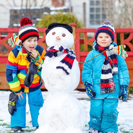 having fun: Two little fiends, kid boys making a snowman, playing and having fun with snow, outdoors  on cold day. Active outdoors leisure with children in winter.