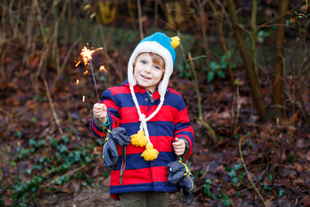 for kids: Little child in winter clothes holding burning sparkler on New Years Eve. Safe fireworks for kids concept. Happy kid boy outdoors.