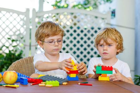 familias unidas: Dos amigos rubios que juegan con un montón de bloques de plástico de colores interiores. Muchachos niños activos, los hermanos que se divierten con la construcción y la creación de juntas.