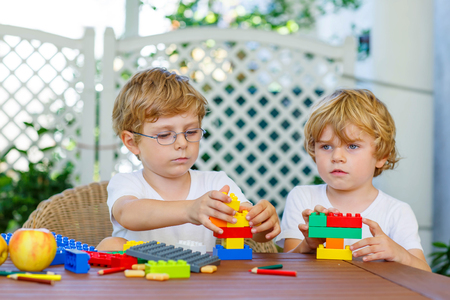 together: Two little blond friends playing with lots of colorful plastic blocks indoor. Active kid boys, siblings having fun with building and creating together. Stock Photo