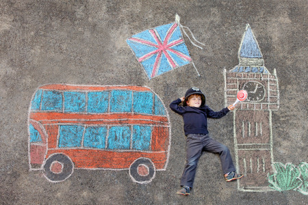 chalks: Happy little kid boy in british policeman uniform having fun with London picture drawing with colorful chalks. With Big Ben, Union Jack and red bus.