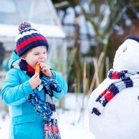 having fun in the snow: Happy little toddler boy making a snowman and eating carrot, playing and having fun with snow, outdoors  on cold day. Active outdoors leisure with kids in winter. Stock Photo