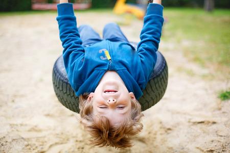 Divertido muchacho feliz niño preescolar se divierten swing de la cadena en el patio al aire libre. balanceándose en cálido día soleado de verano niño. Turismo activo con los niños. Familia, estilo de vida, el concepto de verano