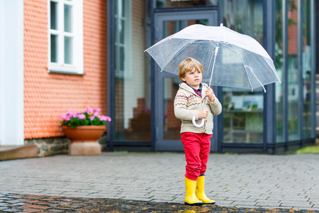 rainy season: Little blond kid boy walking with big umbrella outdoors on rainy day. Child having fun and wearing colorful waterproof clothes and rain boots. Stock Photo