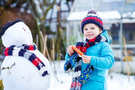 having fun in the snow: Beautiful little kid boy making a snowman and eating carrot, playing and having fun with snow, outdoors  on cold day. Active outdoors leisure with children in winter.