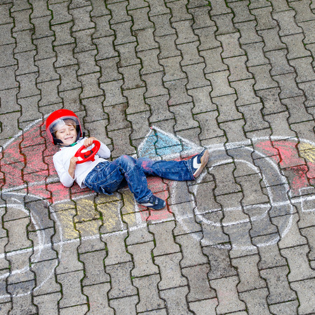 having fun: Active preschool boy having fun with race care picture drawing with colorful chalks. Creative leisure for children outdoors in summer Stock Photo