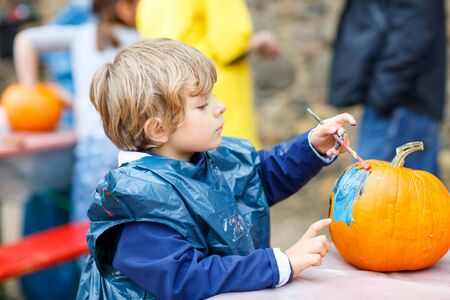 children painting: Happy little kid boy on a harvest festival, painting with colors a pumpkin. Child celebrating traditional festival halloween or thanksgiving. Stock Photo