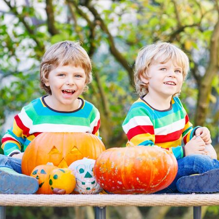 Two little friends boys making jack-o-lantern for halloween in autumn garden, outdoors. Happy family having fun together Banco de Imagens