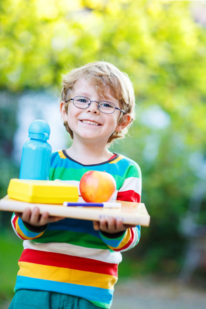 Happy little kid boy with books, apple and drink bottle on his first day to elementary school or nursery. Outdoors.  Back to school, kids, lifestyle concept Stock Photo