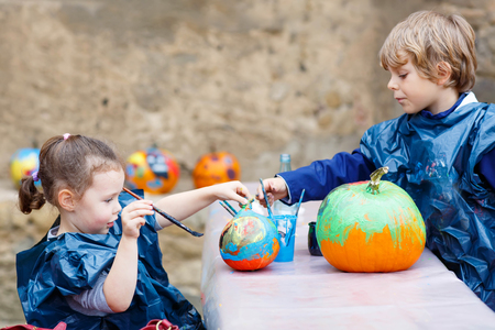 children painting: Two little kids, boy and girl on a harvest festival, painting with colors a pumpkin. Children celebrating traditional festival halloween or thanksgiving.