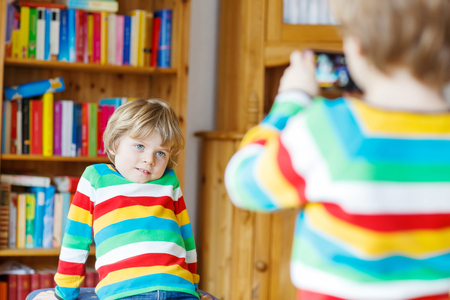photocamera: Two little kid boys making photos with photocamera, indoors. Children wearing colorful shirt. Lifestyle in a daycare or at home. Stock Photo