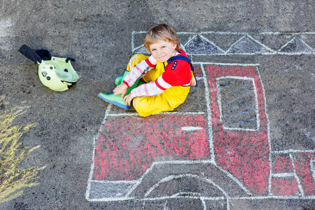 kids having fun: Creative leisure for kids: adorable child of four years having fun with fire truck picture drawing with chalk, outdoors. Dreaming of future profession.