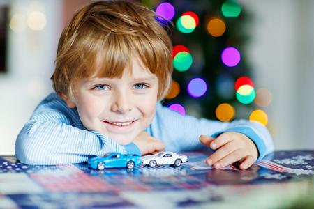 junge: Entzückendes Kind, Junge, der mit Autos und Spielzeug zu Hause, Innen. Lustiges Kind, das Spaß mit Geschenken. Bunte Weihnachtsbeleuchtung auf den Hintergrund. Familie, Urlaub, Kinder Lifestyle-Konzept.