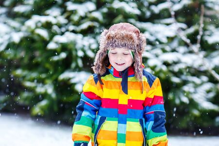 outoors: Portrait of beautiful child in winter clothes with stripes, outdoors, during snowfall on cold day. Active outoors leisure with children in winter.