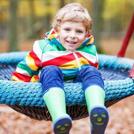 kiddies: Little child in colorful rain jacket with stripes and gumboots having fun with playing chain swing on playground on warm, autumn day, outdoors