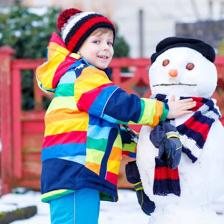 having fun in the snow: Adorable kid boy making a snowman and eating carrot, playing and having fun with snow, outdoors  on cold day. Active outdoors leisure with kids in winter. Stock Photo