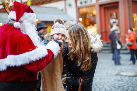 young: Little toddler girl with mother on Christmas market. Funny happy kid taking gift from bag of Santa Claus. holidays, christmas, childhood and people concept