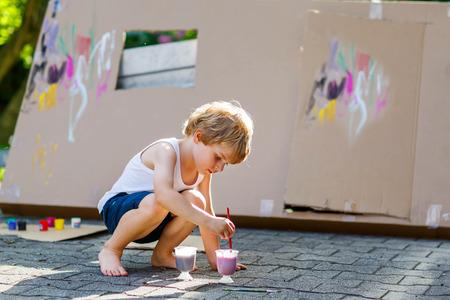 Schattig klein kind jongen schilderij grote papieren huis met kleurrijke paintbox. Kinderen plezier buitenshuis. Creatieve vrijetijdsbesteding, voorschoolse project voor de pupil. Stockfoto
