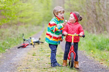 Little girl and boy playing together in forest in bright jackets on a rainy day with bikes. Friendship between siblings. Happy family concept