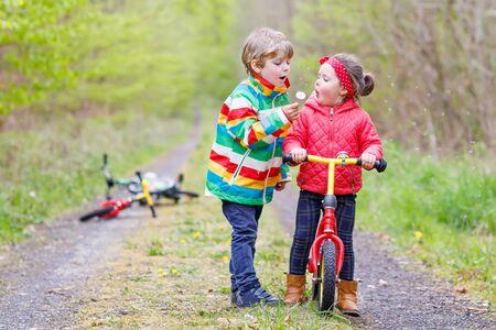 jolie fille: Petite fille et gar�on jouant ensemble dans la for�t dans des vestes lumineuses sur un jour de pluie avec des v�los. Amiti� entre fr�res et s?urs. Concept de famille heureuse