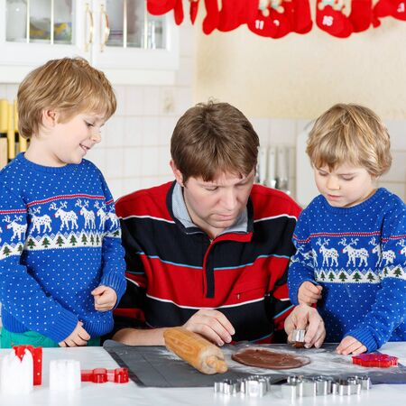 pullovers: Two funny boys and dad baking gingerbread cookies. Happy siblings, children in blue xmas pullovers. Kitchen decorated for Christmas. Family, holiday, kids lifestyle conceplt.
