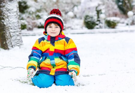 having fun in the snow: Funny preschool boy in colorful clothes happy about snow, playing and having fun, outdoors during snowfall on cold day. Active outoors leisure with children in winter.