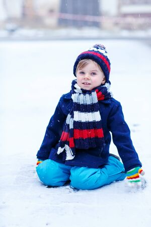 outoors: Cute little funny boy in colorful winter clothes having fun with snow, outdoors during snowfall. Active outoors leisure with children in winter. Kid with warm hat, hand gloves and scarf with stripes. Happiness about snow. Stock Photo