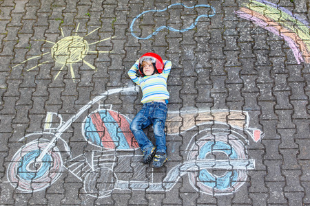 fun: Creative leisure for children: Funny little child of four years in helmet having fun with motorcycle picture drawing with colorful chalks. Children, lifestyle, fun concept.