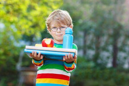ni�o escuela: El ni�o peque�o feliz con los libros, la manzana y la botella de la bebida en su primer d�a a la escuela o guarder�a. Al aire libre. Volver a la escuela, los ni�os, el concepto de estilo de vida