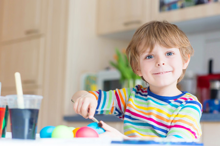 egg hunt: Happy little blond kid boy coloring eggs for Easter holiday in domestic kitchen, indoors. Child having fun and celebrating feast.
