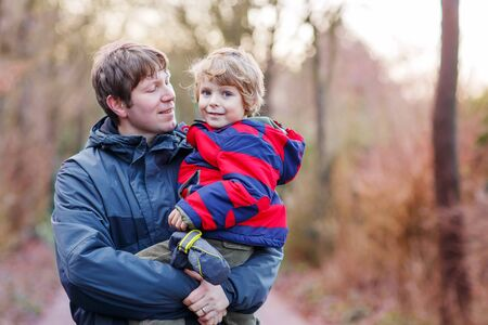looking at baby: Happy dad holding his son, little funny kid boy on arm, on cold day, walking together in a park in spring, autumn or winter. Happy, joyful family.