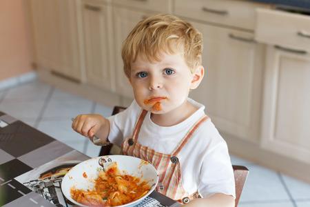 ragazze bionde: Adorabile bambino di due anni di mangiare la pasta coperta. bambino del bambino in cucina domestica o in vivaio. Bambino sveglio e cibo sano. Archivio Fotografico