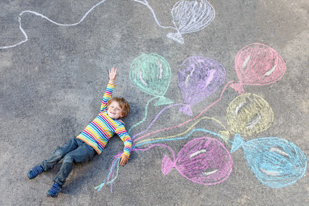 chalk drawing: Cute little kid boy playing and flying with colorful balloons picture drawing with chalk. Creative leisure for children outdoors in summer, celebrating birthday