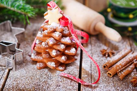 Selbst gemachter gebackener Weihnachtslebkuchenbaum auf hölzernem Hintergrund der Weinlese. Anis, Zimt, Backrolle, Sternformen und Dekorationsutensilien. Mit Puderzucker als Schnee. Selfmade Geschenk für Weihnachten. Standard-Bild - 47055864