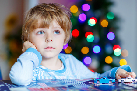 toys: Adorable child playing with cars and toys at home, indoor. funny boy having fun with gifts. Colorful christmas lights on background. Family, holiday, kids lifestyle concept.