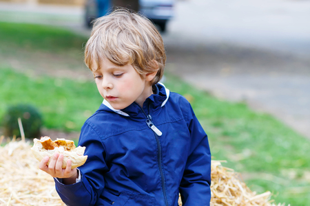 german sausage: Beautiful adorable little kid boy eating hot dog or German sausage on thanksgiving or halloween pumpkin festival, outdoors. child enjoying warm autumn day. Stock Photo