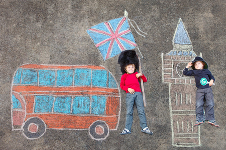 friends having fun: Two funny kid boys in british queens guard soldier and policeman uniform having fun with London picture drawing with colorful chalks. With Big Ben, Union Jack and red bus.