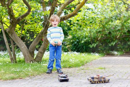 juguetes: Adorable niño pequeño lindo que juega con tanque de juguete, al aire libre. Niño feliz niño que se divierte en día soleado de verano. Ocio, estilo de vida para el concepto de niños.