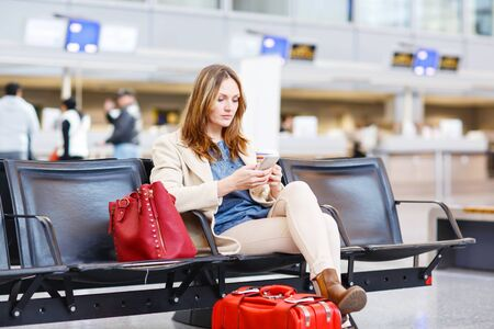 flights: Young woman at international airport sitting waiting for cancelled or delayed flight. Female passenger at terminal, indoors.  Travel, business, people concept. Stock Photo