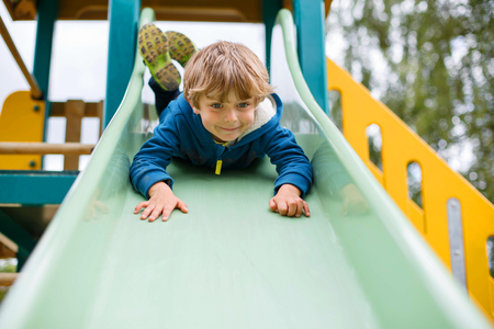 kid portrait: Happy blond kid boy having fun and sliding on outdoor playground. Child smiling. Summer leisure for kids.