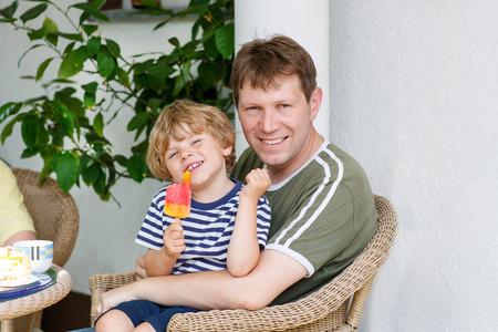 comiendo helado: El niño pequeño niño rubio y joven padre feliz comiendo helado juntos en verano. Familia divertida al aire libre.