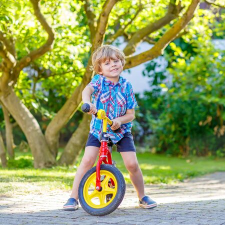 domestic garden: funny blond kid boy driving bicycle in domestic garden. Toddler child dreaming and having fun on warm summer day. Active games for children outdoors.
