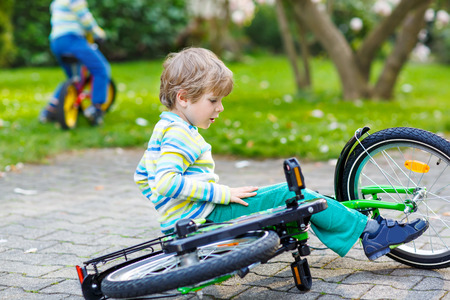 Little kid boy fell down of his first bike in park or garden on warm spring day. Active leisure for kids outdoors. Another child on background