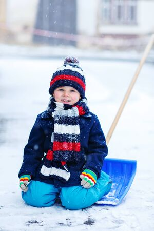 having fun in the snow: Cute little funny boy in colorful winter clothes having fun with snow shovel, outdoors during snowfall. Active outoors leisure with children in winter. Kid with warm hat, hand gloves and scarf with stripes. Happiness about snow.
