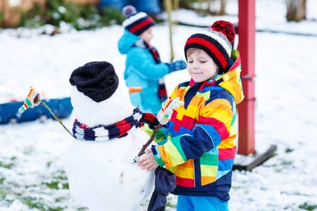 having fun in the snow: Two little siblings boys making a snowman, playing and having fun with snow, outdoors  on cold day. Active outdoors leisure with kids in winter. Stock Photo
