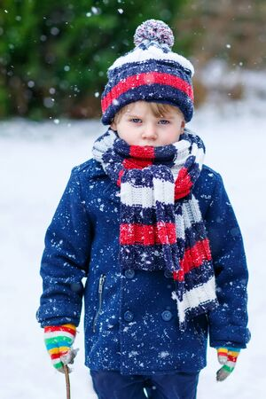outoors: Sad kid boy in colorful winter clothes, outdoors during snowfall. Active outoors leisure with children in winter on cold snowy days